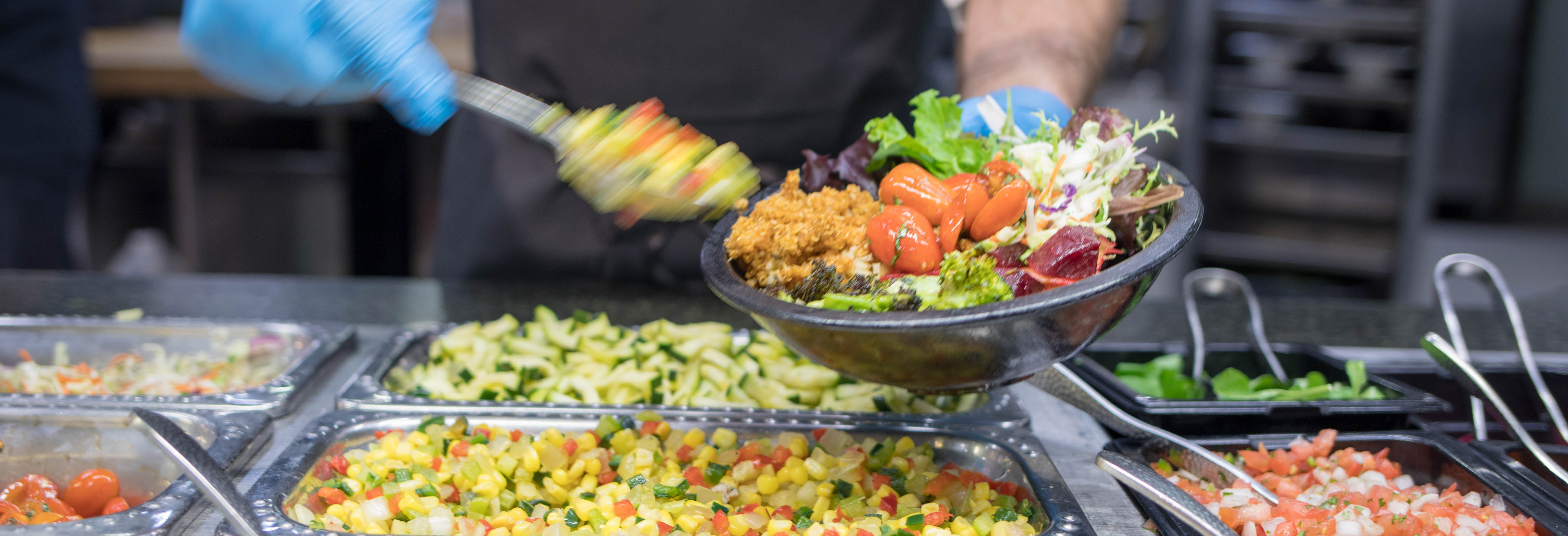 A Dining Services employee prepares a nutritious meal at the Grain Bowl station at Southside Cafe.