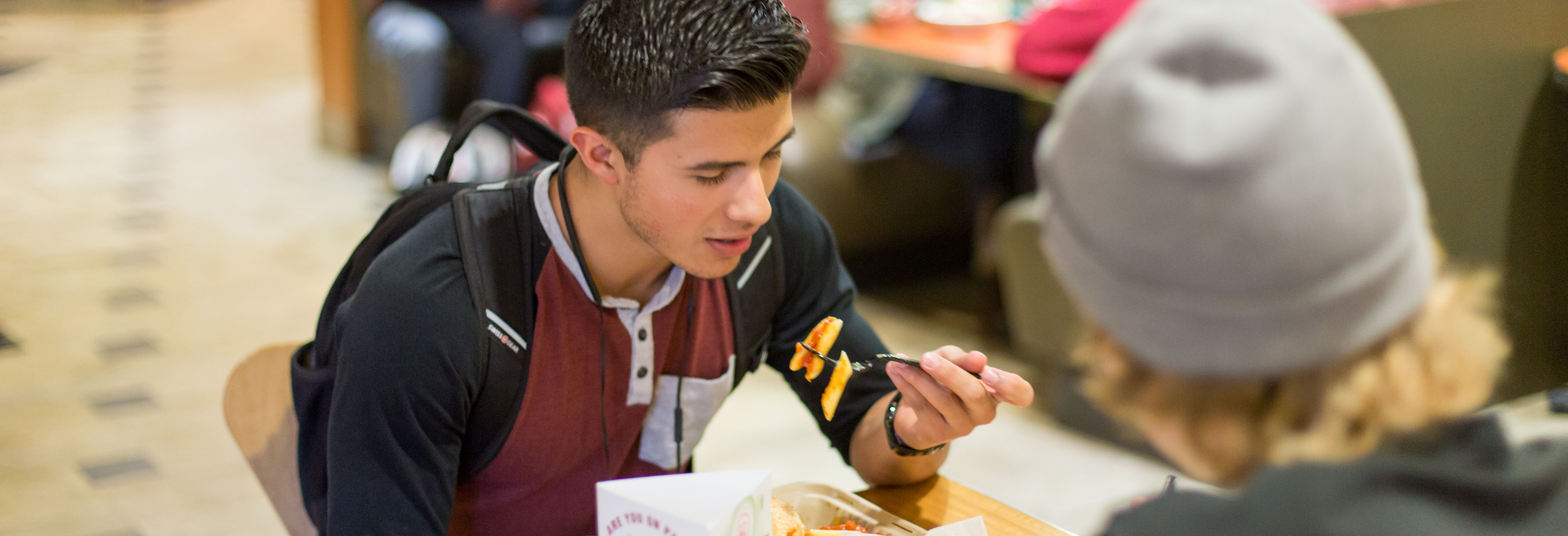 A student enjoys pasta at a dining center.