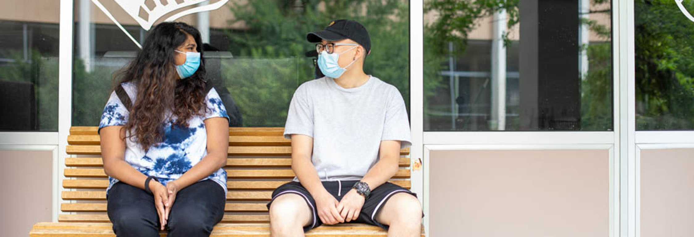 Two students wearing masks sit outside Flix Cafe.