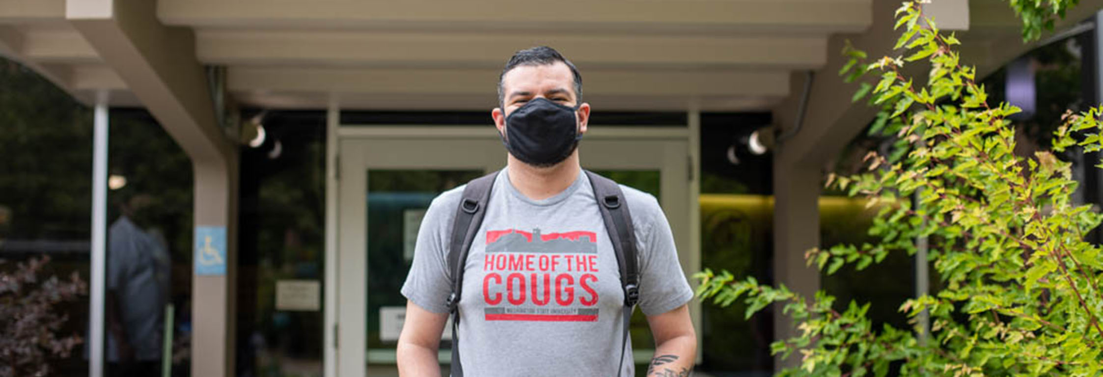 A student wearing a mask & a WSU t-shirt stands outside Southside Cafe.